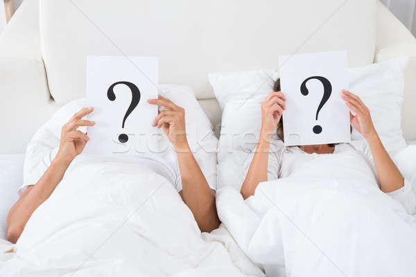 Couple Holding Question Mark Over Faces Stock photo © AndreyPopov