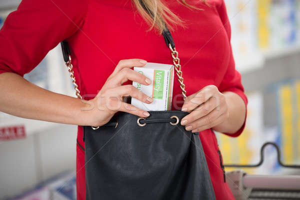 Woman Stealing Capsule Packet At Supermarket Stock photo © AndreyPopov