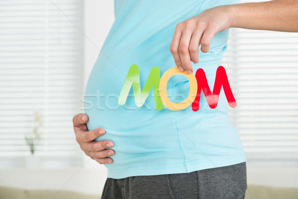 Midsection Of Pregnant Woman Holding Word Mom Stock photo © AndreyPopov