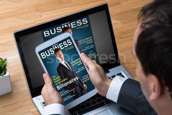 Stock photo: Businessman Reading Business Magazine On Tablet
