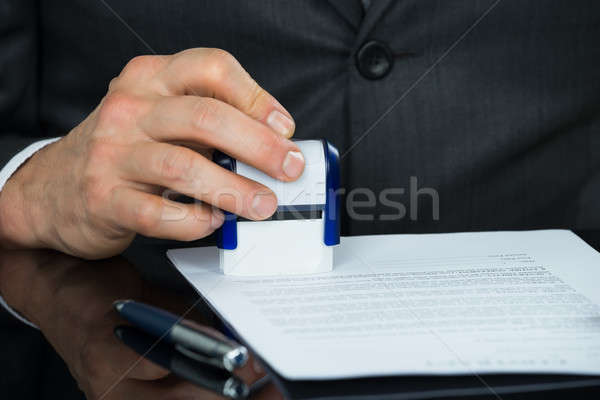 Close-up Of Businessman Stamping Document Stock photo © AndreyPopov