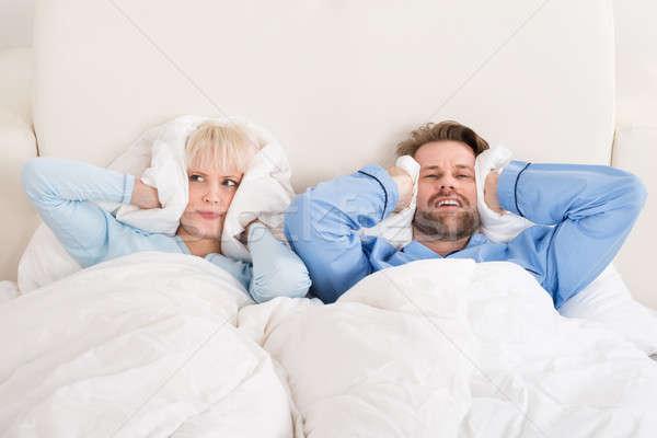 Couple oreilles dormir lit jeunes malheureux Photo stock © AndreyPopov
