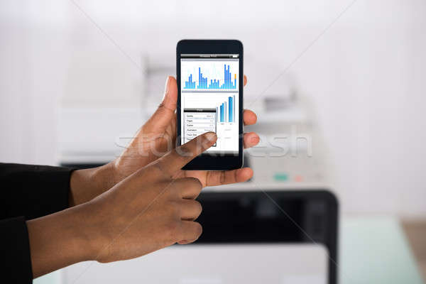 Businesswoman Using Smartphone For Printing Graph Paper Stock photo © AndreyPopov