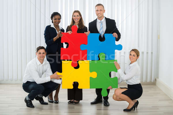 Businesspeople Holding Puzzle Pieces Stock photo © AndreyPopov