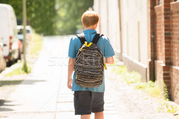 Schooljongen lopen trottoir achteraanzicht rugzak kind Stockfoto © AndreyPopov