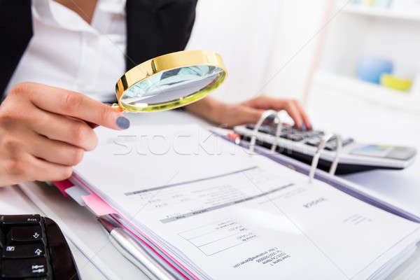 Female Accountant Holding Magnifying Glass To Analyze Bills Stock photo © AndreyPopov