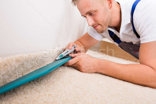 Man Cutting Carpet With Cutter Stock photo © AndreyPopov