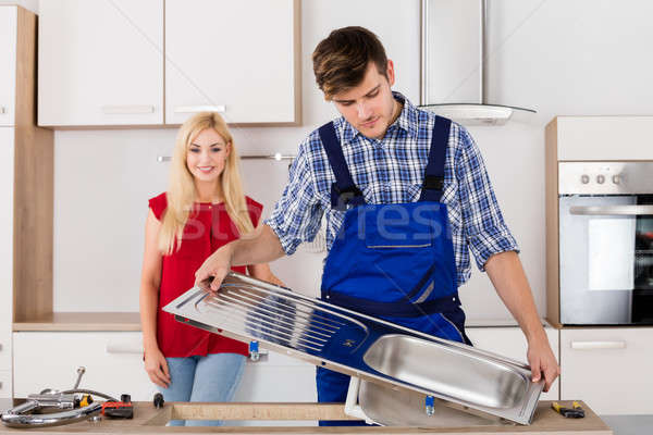 Male Plumber Fixing Stainless Steel Sink In Kitchen Stock photo © AndreyPopov