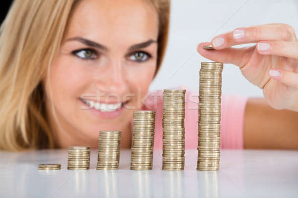 Happy Woman Inserting Coin On The Stacked Of Coins Stock photo © AndreyPopov