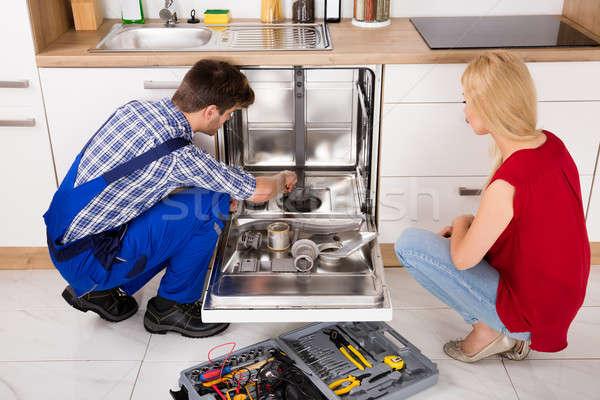 Kadın bakıyor tamir bulaşık makinesi genç kadın Stok fotoğraf © AndreyPopov