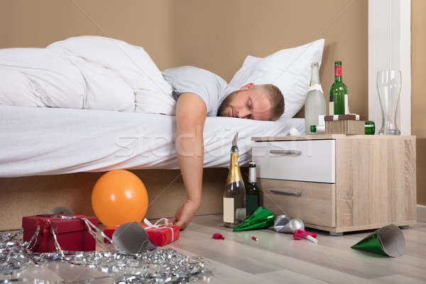 Tired Man Lying On Bed After Party Stock photo © AndreyPopov