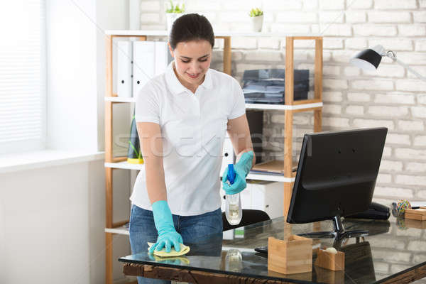Woman Cleaning The Glass Office Desk Stock photo © AndreyPopov