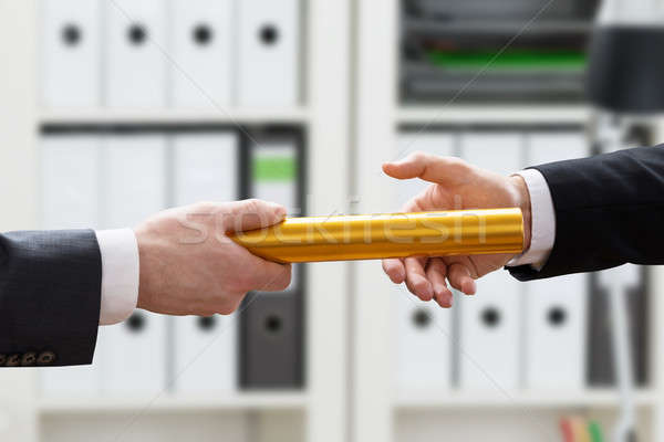 Two Hands Passing A Golden Baton Stock photo © AndreyPopov