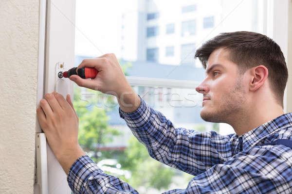 Bricoleur fenêtre tournevis Homme uniforme Photo stock © AndreyPopov