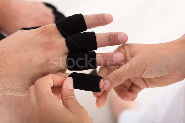 Doctor Putting Finger Protector Sleeve On Man's Finger Stock photo © AndreyPopov