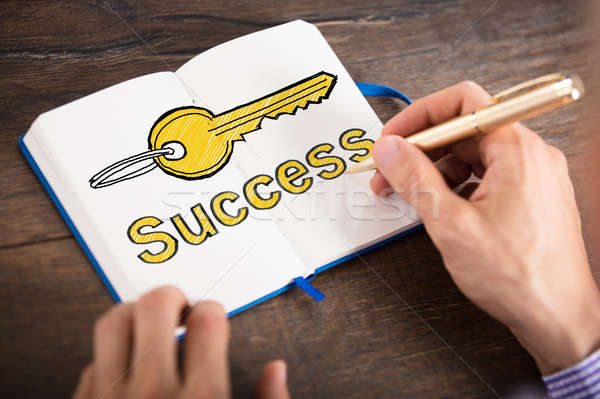 Person Drawing Success Key In Book Stock photo © AndreyPopov