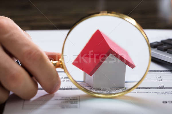 Businessperson With Magnifying Glass Zooming On House Model Stock photo © AndreyPopov