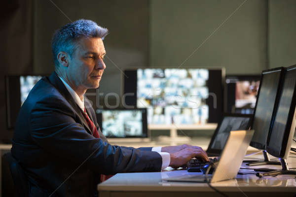 Businessman Looking At CCTV Camera Footage Stock photo © AndreyPopov