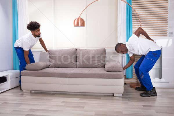 молодые мужчины боль в спине диване гостиной Сток-фото © AndreyPopov