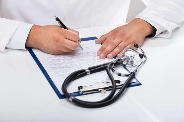 Doctor's hand signing document Stock photo © AndreyPopov