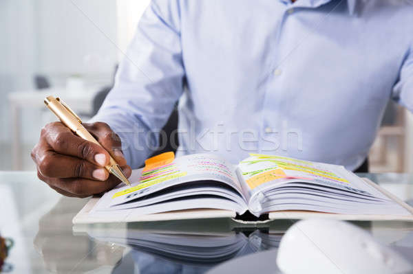 Businessman Writing Schedule In Diary With Pen Stock photo © AndreyPopov