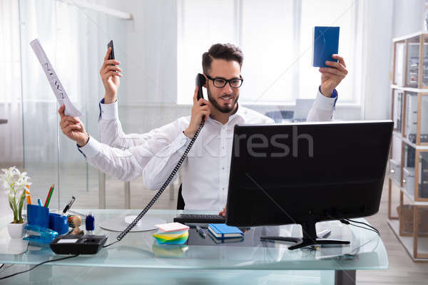 Young Businessman Doing Multitasking Work Stock photo © AndreyPopov