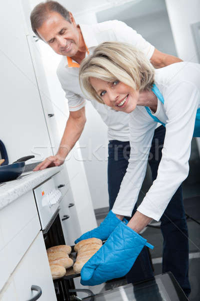 Stock photo: Woman Taking Baking Tray Out From Oven
