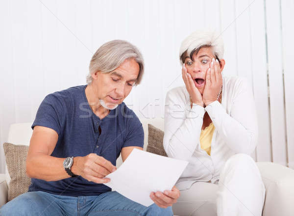 Stock photo: Senior couple discussing a document