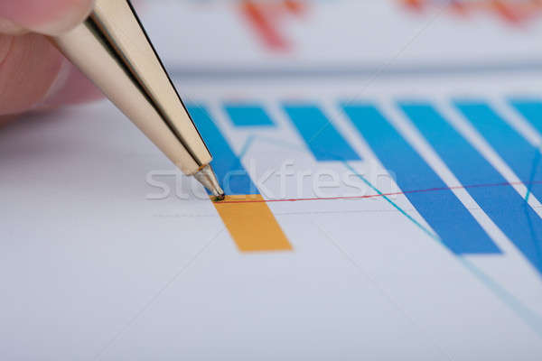 Hand Showing Diagram On Financial Report With Pen Stock photo © AndreyPopov
