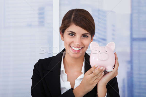 Stock photo: Happy Businesswoman Holding Piggybank In Office