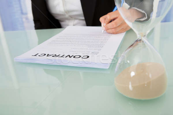Businesswoman Signing Contract With Hourglass At Desk Stock photo © AndreyPopov