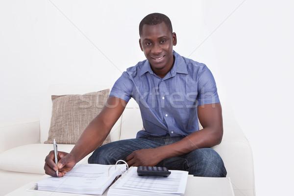 Genç bütçe mutlu Afrika adam oturma Stok fotoğraf © AndreyPopov