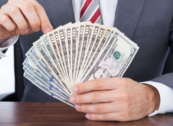 Businessman Holding Fanned Banknotes Stock photo © AndreyPopov