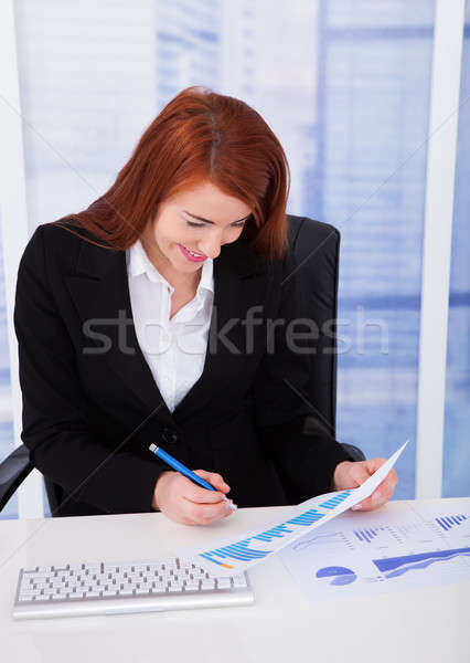 Businesswoman Analyzing Graph At Desk Stock photo © AndreyPopov