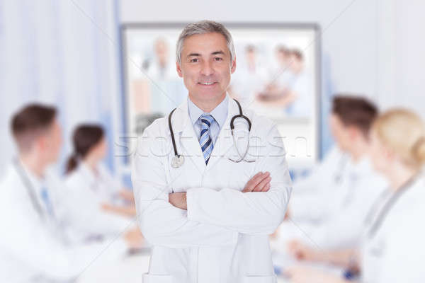 Doctor With Arms Crossed In Meeting Room Stock photo © AndreyPopov