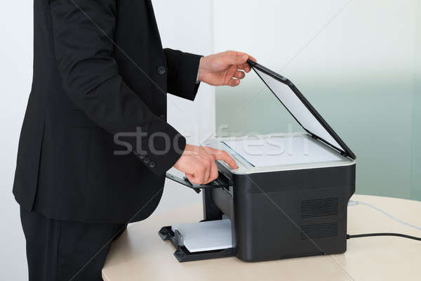 Midsection Of Businessman Using Photocopy Machine In Office Stock photo © AndreyPopov
