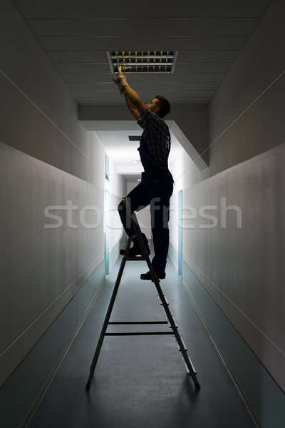 Electrician On Stepladder Installs Lighting To The Ceiling Stock photo © AndreyPopov