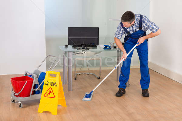 Man Mopping Office With Wet Floor Sign Stock photo © AndreyPopov