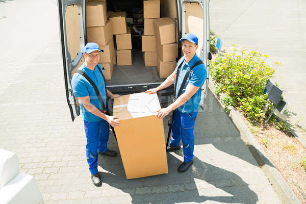 Stock photo: Two Movers Loading Boxes In Truck