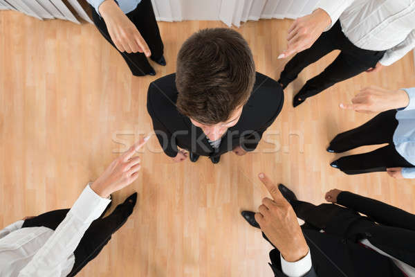 Businesspeople Pointing At Businessman Stock photo © AndreyPopov