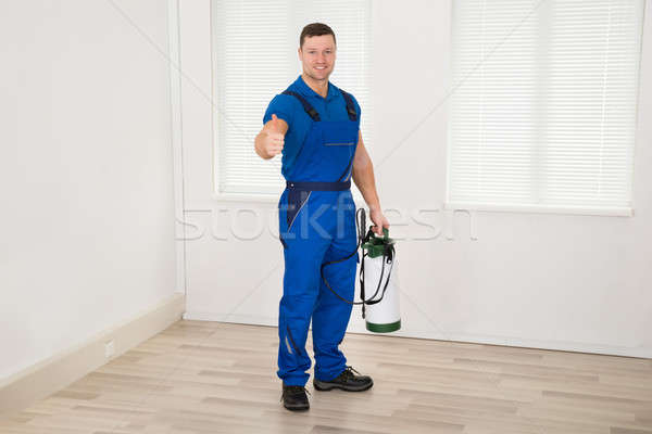 Smiling Male Worker Holding Pesticide Container At Home Stock photo © AndreyPopov