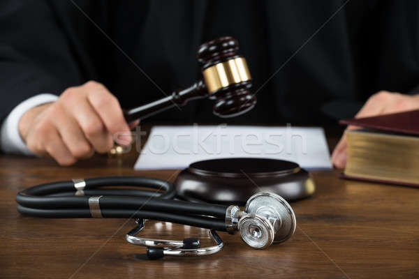 Judge Striking Mallet With Stethoscope At Desk Stock photo © AndreyPopov