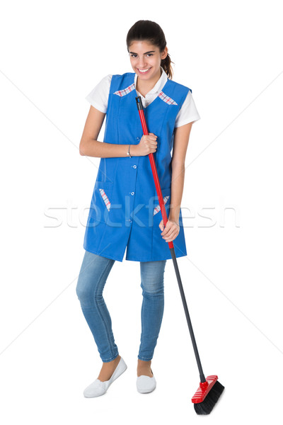 Happy Female Janitor Sweeping On White Background Stock photo © AndreyPopov