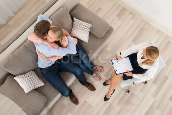 Couple Sitting On Sofa Embracing In Front Of Psychologist Stock photo © AndreyPopov