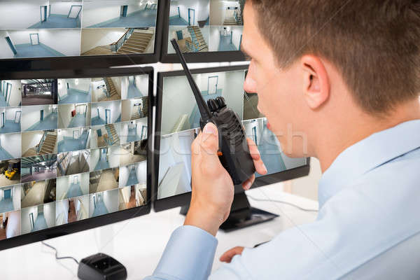 Male Security Guard Talking On Walkie-talkie Stock photo © AndreyPopov