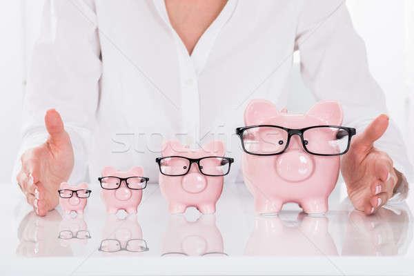 Person's Hand Protecting Piggybanks On Desk Stock photo © AndreyPopov