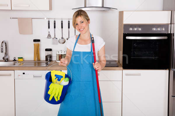 Housemaid Holding Cleaning Equipment In Kitchen Stock photo © AndreyPopov