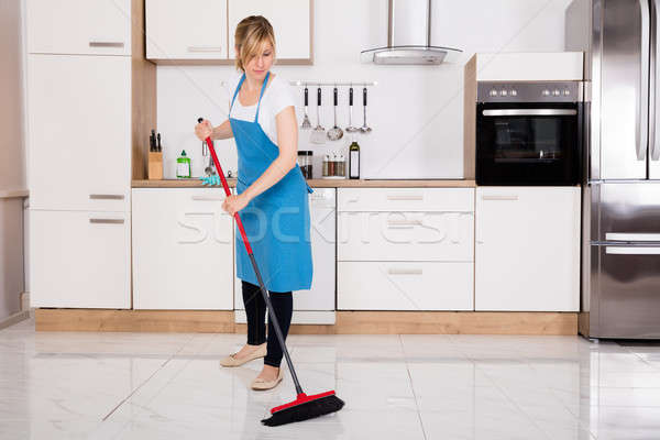 Housemaid Sweeping Floor In Kitchen Stock photo © AndreyPopov