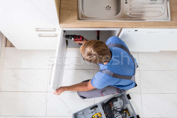 Man In Overall Repairing Cabinet Stock photo © AndreyPopov