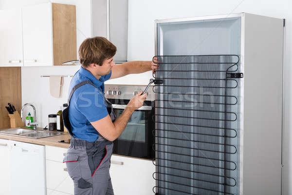 Dolgozik hűtőszekrény csavarhúzó átfogó konyha munka Stock fotó © AndreyPopov